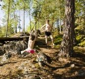 Pequeño muchacho lindo que salta con el amortiguador auxiliar en el bosque, entrenando con el papá, la familia feliz el vacacione Imagen de archivo