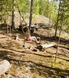 Pequeño muchacho lindo que salta con el amortiguador auxiliar en el bosque, entrenando con el papá, la familia feliz el vacacione Fotos de archivo libres de regalías