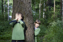 Pequeño muchacho lindo que se coloca en el árbol. Foto de archivo libre de regalías