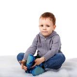 Pequeño muchacho lindo que se sienta en el piso que muerde su labio más bajo Fotografía de archivo