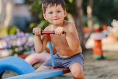 Pequeño muchacho lindo sin la camisa que juega en el patio, montando un oscilación de madera imagenes de archivo
