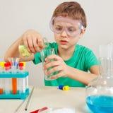 Pequeño muchacho pensativo en las gafas de seguridad que hacen experimentos químicos en laboratorio fotografía de archivo