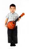 Pequeño muchacho pensativo feliz que toca la guitarra Fotos de archivo