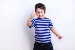 Pequeño muchacho precioso que señala en algo, lanzamiento del estudio en blanco imagen de archivo