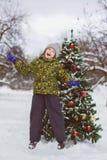 Pequeño muchacho preescolar lindo que salta o que juega cerca del árbol de navidad al aire libre Fotos de archivo libres de regalías