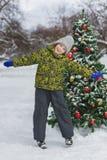 Pequeño muchacho preescolar lindo que salta o que juega cerca del árbol de navidad al aire libre Fotografía de archivo