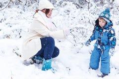 Pequeño muchacho preescolar y su madre que juegan con la primera nieve en p Imagen de archivo libre de regalías