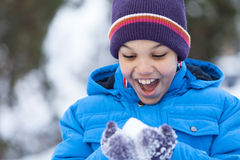 Pequeño muchacho que celebra nieve y la sonrisa Imagenes de archivo