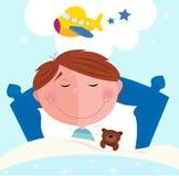 Pequeño muchacho que duerme en la cama que soña sobre el aeroplano Foto de archivo libre de regalías