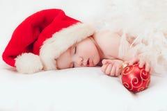 Pequeño muchacho que duerme en un casquillo del Año Nuevo Imagen de archivo libre de regalías