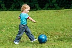 Pequeño muchacho que juega al balompié en el parque al aire libre Fotos de archivo