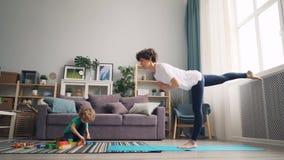 Pequeño muchacho que juega con los bloques mientras que muchacha bonita de la madre que hace el equilibrio de la yoga almacen de metraje de vídeo