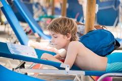 Pequeño muchacho que lee un libro en una silla de cubierta Imagen de archivo