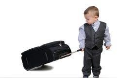 Pequeño muchacho que lleva una maleta Foto de archivo libre de regalías
