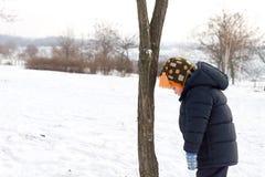 Pequeño muchacho que mira abajo la nieve del invierno Imágenes de archivo libres de regalías