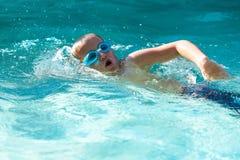 Natación joven del muchacho en piscina. Fotografía de archivo