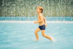 Pequeño muchacho que se divierte que corre en piscina fotografía de archivo libre de regalías