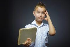 Pequeño muchacho que se pregunta hermoso con el libro aislado en fondo gris Imagen de archivo