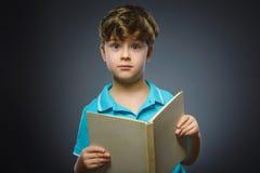 Pequeño muchacho que se pregunta hermoso con el libro aislado en fondo gris Imágenes de archivo libres de regalías