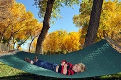 Pequeño muchacho que se reclina en hamaca Fotos de archivo libres de regalías