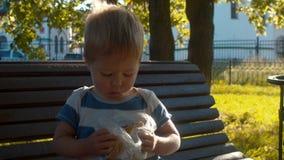 Pequeño muchacho que se sienta en un banco y que come el bollo metrajes