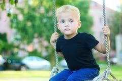 Pequeño muchacho rubio adorable que se divierte en el patio Fotos de archivo libres de regalías