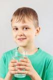 Pequeño muchacho rubio con el vidrio de agua mineral fresca Imagen de archivo