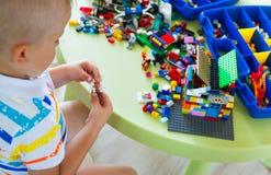 Pequeño muchacho rubio del niño que juega con las porciones de bloque plástico colorido Foto de archivo libre de regalías