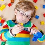 Pequeño muchacho rubio del niño que juega con las porciones de bloque plástico colorido Fotografía de archivo libre de regalías
