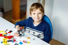 Pequeño muchacho rubio del niño que juega con las porciones de bloques plásticos coloridos foto de archivo libre de regalías