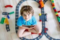 Pequeño muchacho rubio del niño que juega con los bloques coloridos del plástico y que crea la estación de tren Imagen de archivo libre de regalías