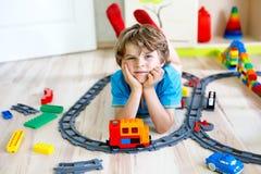 Pequeño muchacho rubio del niño que juega con los bloques coloridos del plástico y que crea la estación de tren Fotografía de archivo libre de regalías