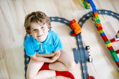 Pequeño muchacho rubio del niño que juega con los bloques coloridos del plástico y que crea la estación de tren Fotos de archivo
