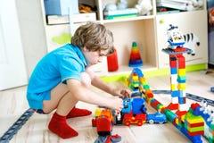Pequeño muchacho rubio del niño que juega con los bloques coloridos del plástico y que crea la estación de tren Imagen de archivo