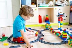 Pequeño muchacho rubio del niño que juega con los bloques coloridos del plástico y que crea la estación de tren Fotografía de archivo