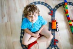 Pequeño muchacho rubio del niño que juega con los bloques coloridos del plástico y que crea la estación de tren Foto de archivo