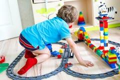 Pequeño muchacho rubio del niño que juega con los bloques coloridos del plástico y que crea la estación de tren Imagenes de archivo
