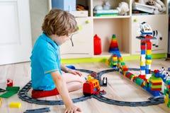 Pequeño muchacho rubio del niño que juega con los bloques coloridos del plástico y que crea la estación de tren Foto de archivo libre de regalías