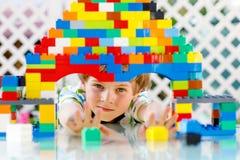 Pequeño muchacho rubio del niño y del niño que juega con las porciones de bloques plásticos coloridos Fotografía de archivo libre de regalías