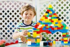 Pequeño muchacho rubio del niño y del niño que juega con las porciones de bloques plásticos coloridos Foto de archivo libre de regalías