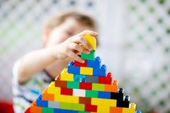 Pequeño muchacho rubio del niño y del niño que juega con las porciones de bloques plásticos coloridos Fotos de archivo libres de regalías