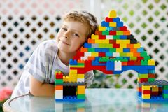 Pequeño muchacho rubio del niño y del niño que juega con las porciones de bloques plásticos coloridos Imágenes de archivo libres de regalías