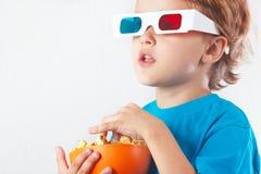 Pequeño muchacho rubio en los vidrios 3D con el cuenco de palomitas Foto de archivo