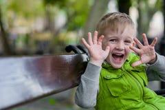 Pequeño muchacho rubio feliz emocionado con las manos abiertas para arriba Fotos de archivo libres de regalías