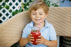 Pequeño muchacho rubio que bebe el jugo sano de la sandía en verano Imagenes de archivo
