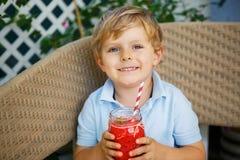 Pequeño muchacho rubio que bebe el jugo sano de la sandía en verano Foto de archivo libre de regalías