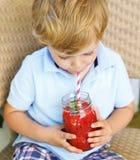 Pequeño muchacho rubio que bebe el jugo sano de la sandía en verano Fotos de archivo