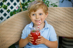 Pequeño muchacho rubio que bebe la sandía sana  Fotos de archivo libres de regalías