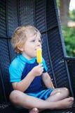 Pequeño muchacho rubio que come el helado amarillo Fotos de archivo