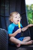 Pequeño muchacho rubio que come el helado amarillo Foto de archivo libre de regalías